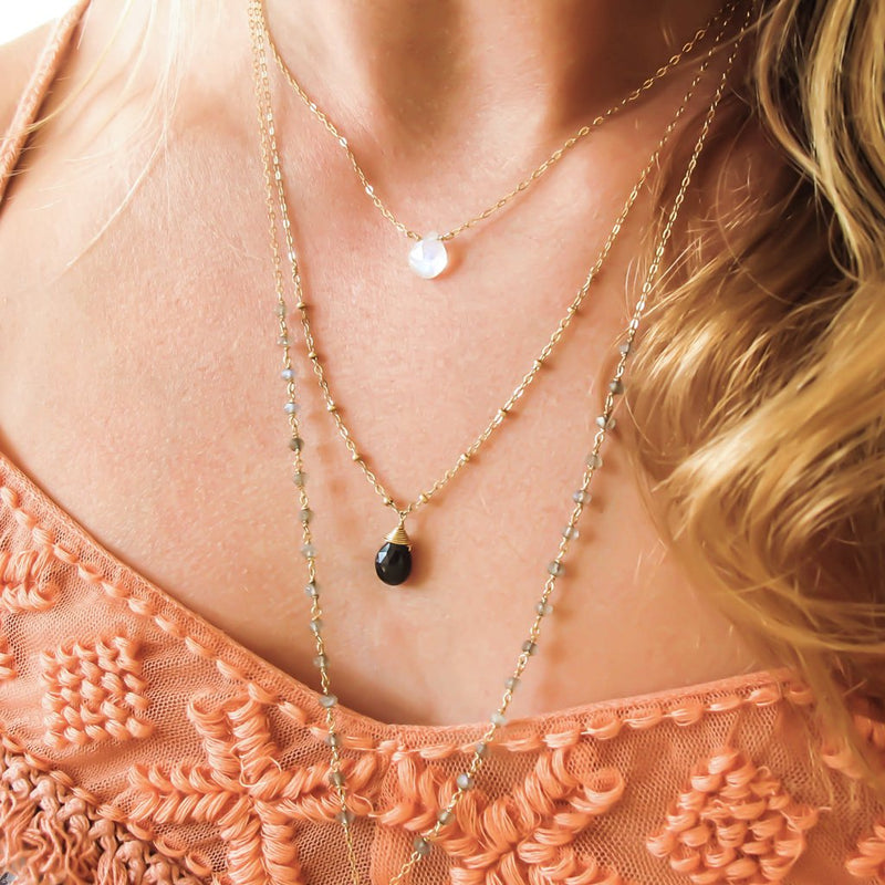 layered gold chain necklaces with moonstone black spinel and labradorite by delia langan jewelry