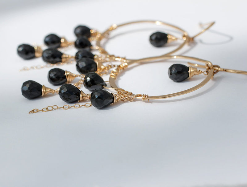 black spinel closeup of 14k gold filled black spinel cascade gemstone hoops laying on a grey surface