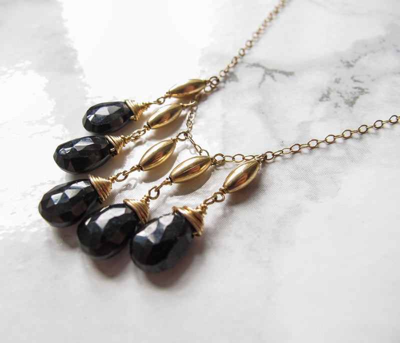 closeup of a 14k gold filled black spinel cascade gemstone necklace laying on a shiny white surface
