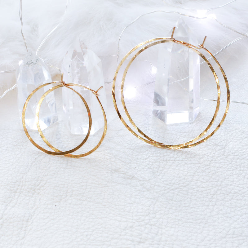 two pairs of small and medium gold hoop earrings leaning against crystals on white leather surface