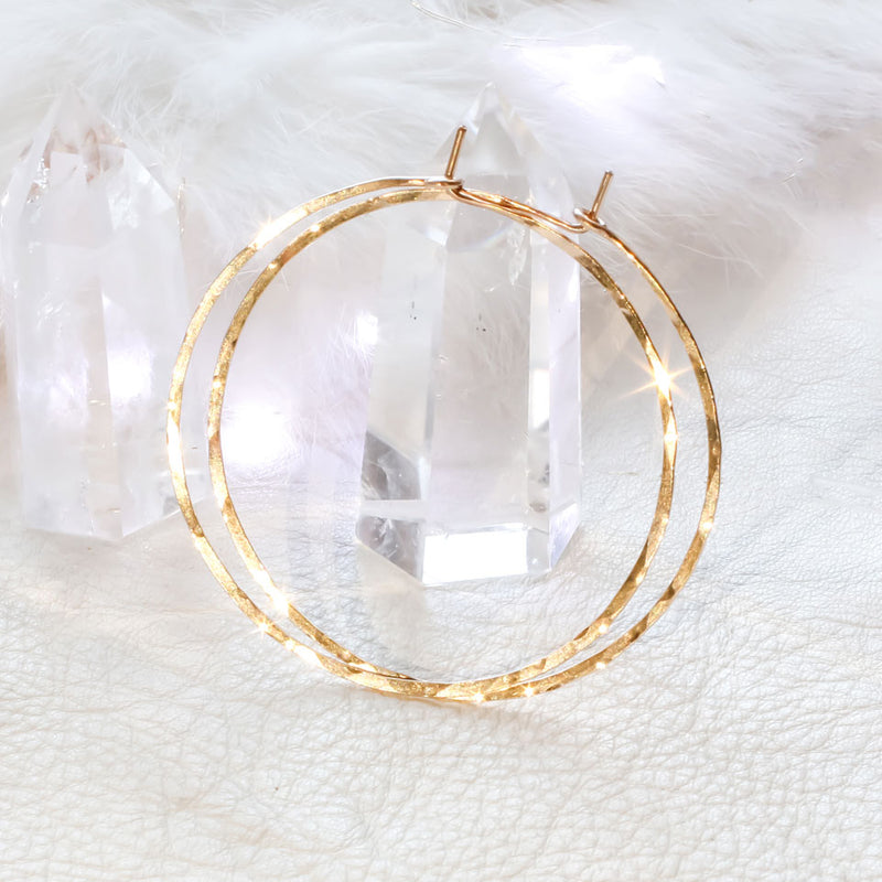 14k gold filled 2 inch endless thin hoop earrings laying on crystal quartz under a shiny bright light on white surface