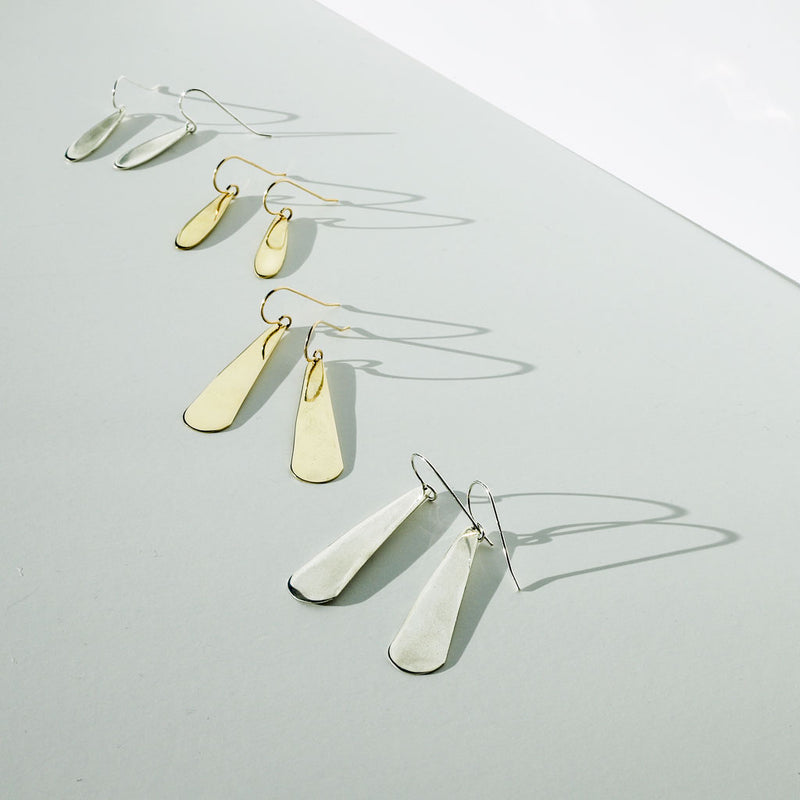 gold and silver teardrop earrings in different sizes by delia langan