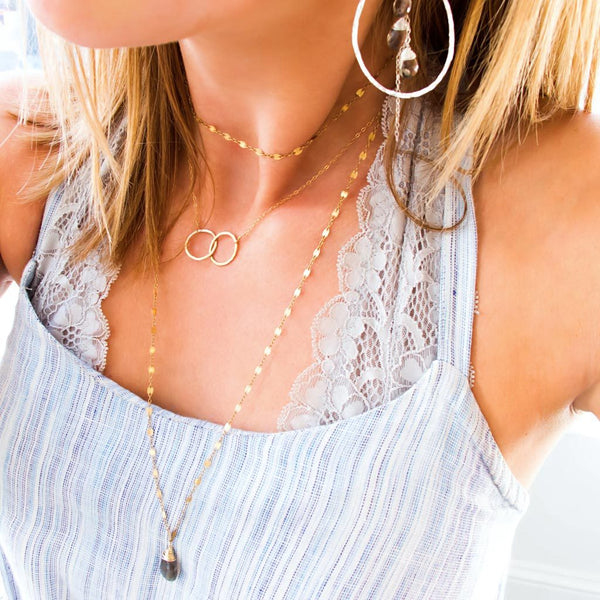 neckline of girl with layered long and short delicate gold necklaces with interlocking infinity necklace and gemstone hoop earrings in a blue dress