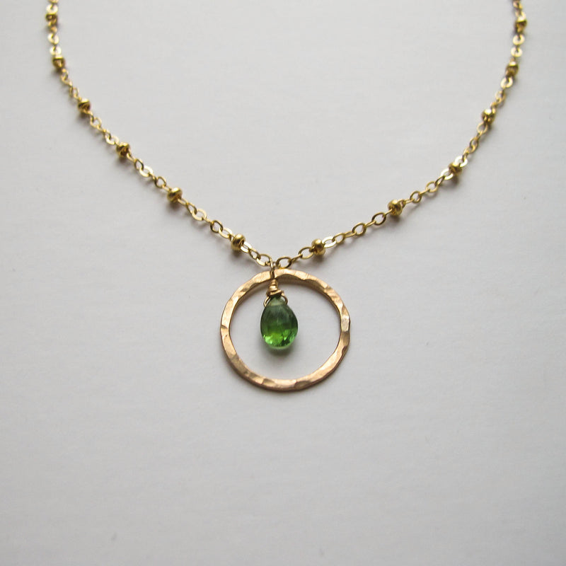 14k gold filled green tourmaline unity gemstone necklace on a grey surface