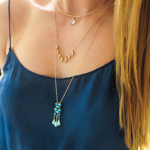 long turquoise necklace on gold chain by delia langan jewelry