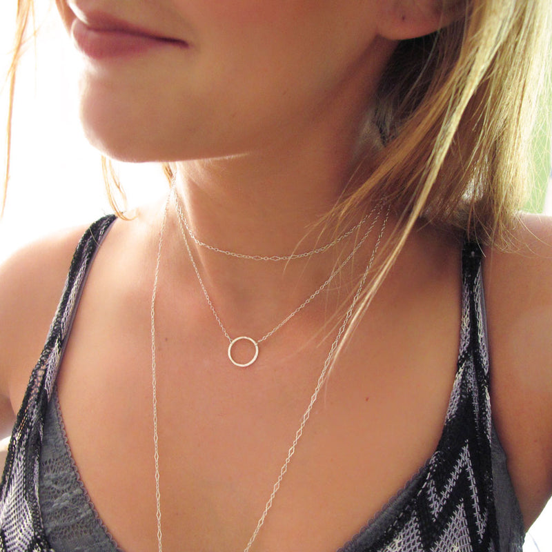girl with delicate silver circle necklace and layered dainty silver chains