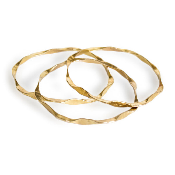 three brass im hammered wavy bangles on a white surface