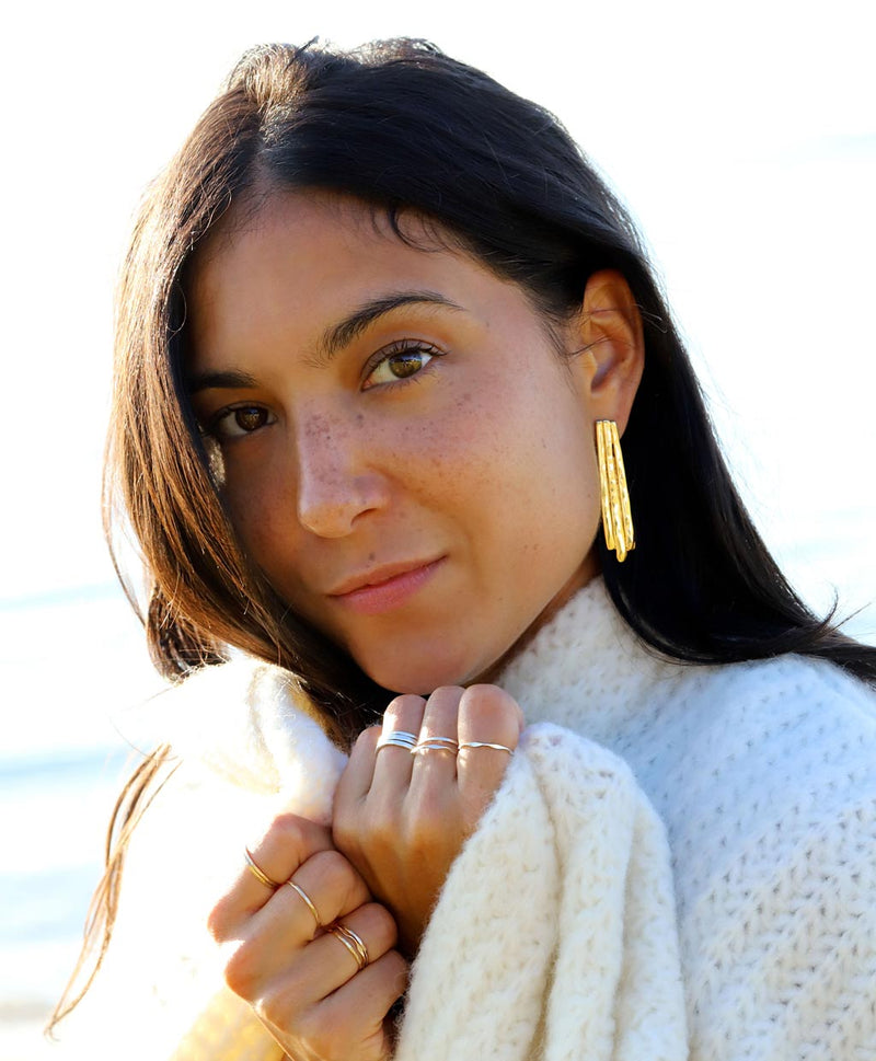 brunette wearing a white wool sweater with gold brass long fringe post earrings on a shiny day