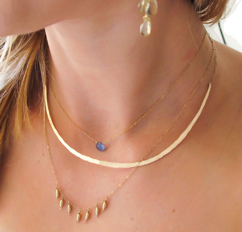 neck closeup of a blond woman wearing a 14k gold filled crescent collar necklace