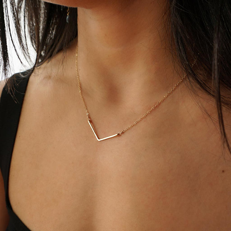 delicate gold v shaped pendant by delia langan jewelry