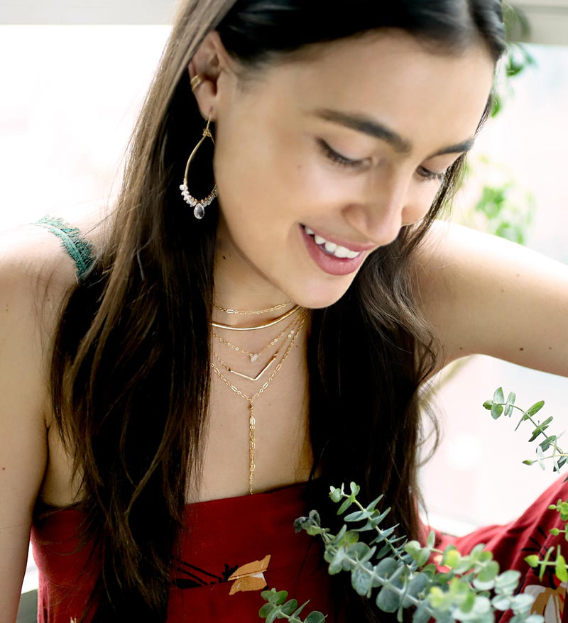 brunette surrounded by branches of leaves on a red top looking down wearing a 14k gold filled wide v necklace