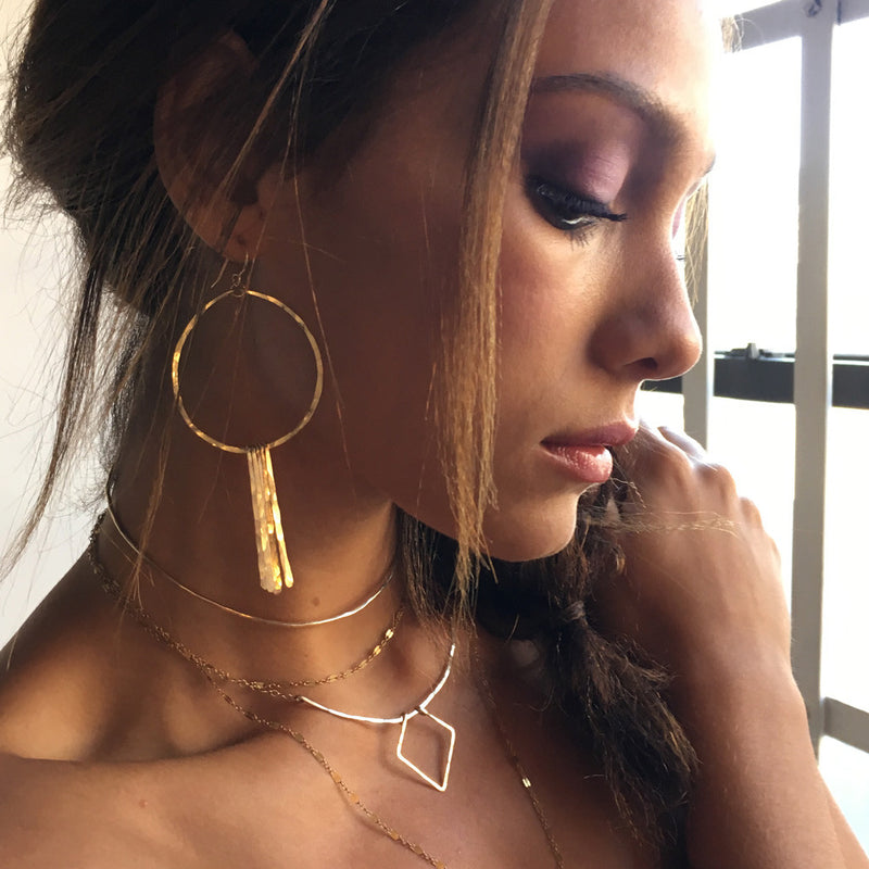 brunette looking down wearing 14k gold filled xl round fringe hoops