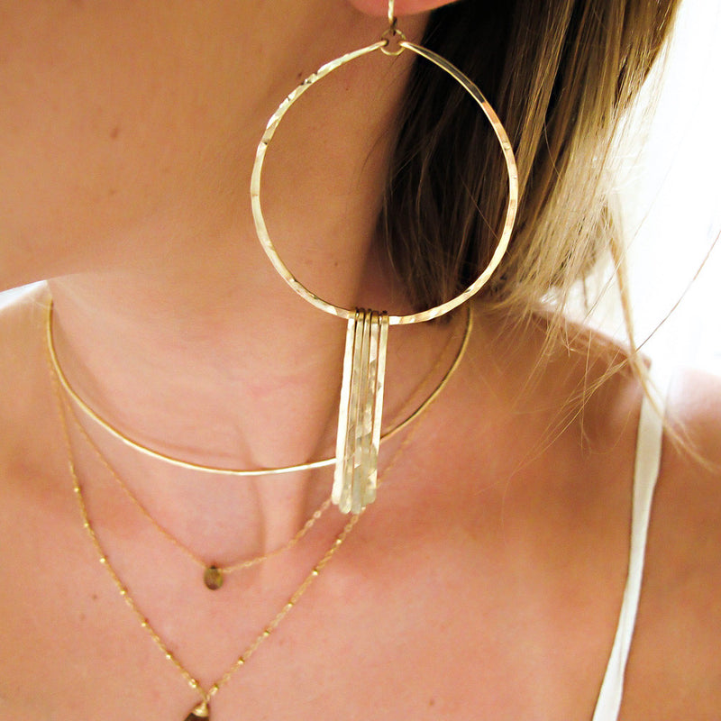 blond woman ear closeup wearing 14k gold filled xl round fringe hoops