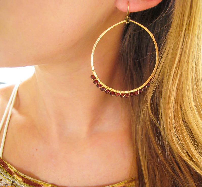 wire wrapped garnet and 14k gold filled large hammered gold hoop earrings by delia langan jewelry