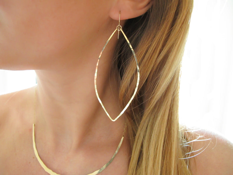 blond woman neck closeup wearing 14k gold filled xl leaf hoop earrings and 14k gold filled crescent collar necklace