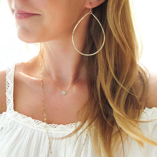 girl with large teardrop hoop earrings and delicate blue gemstone necklace