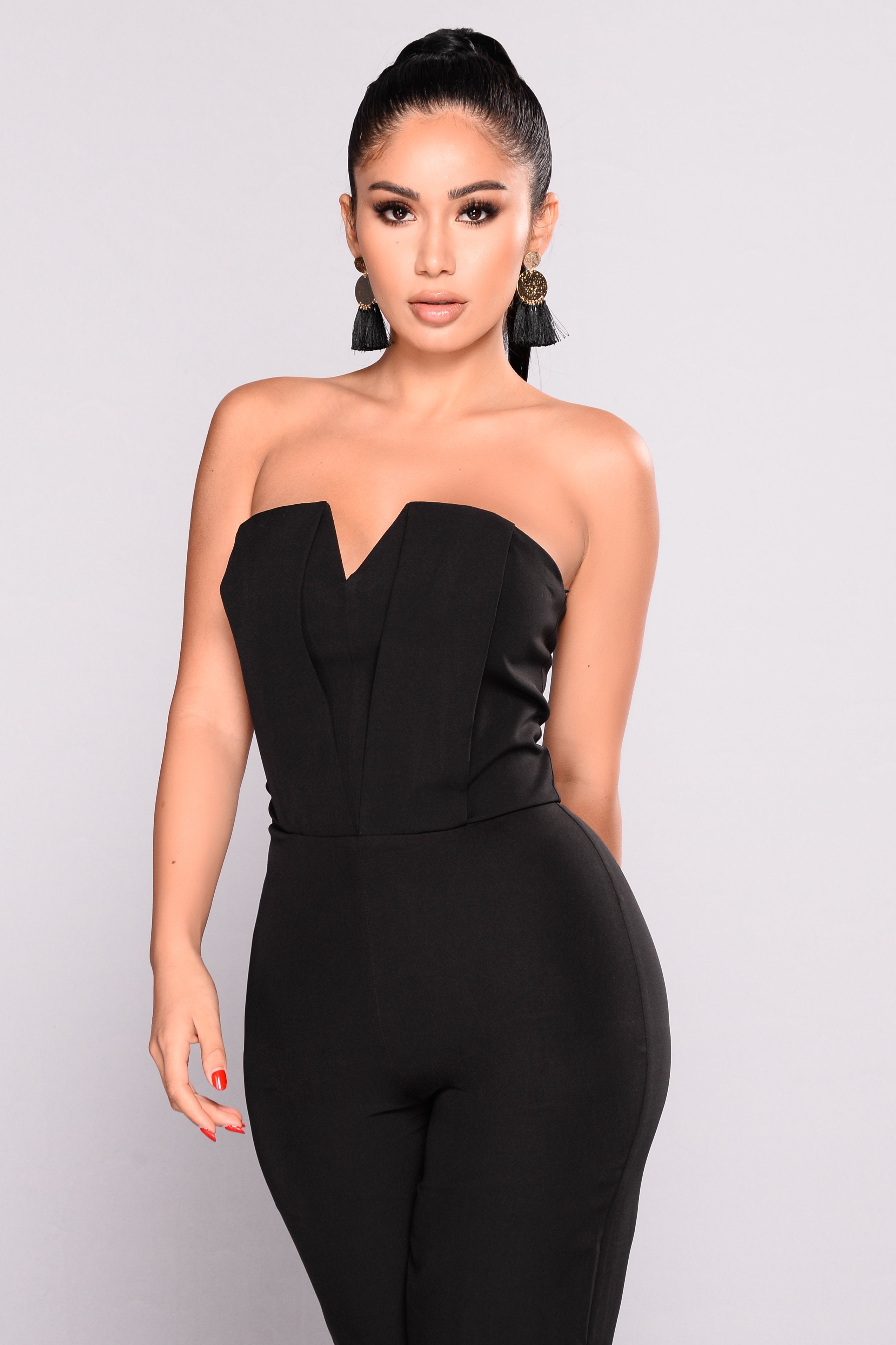 Close up of a model wearing a black, strapless tube jumpsuit from Fashion Nova.