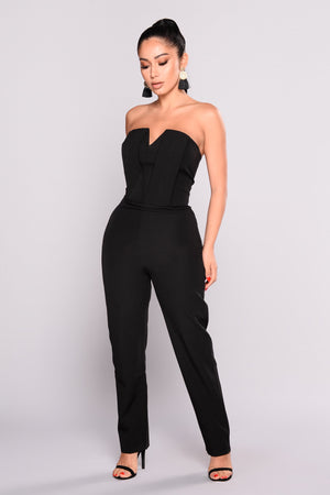 Full length view of a model wearing a black, strapless tube jumpsuit from Fashion Nova.