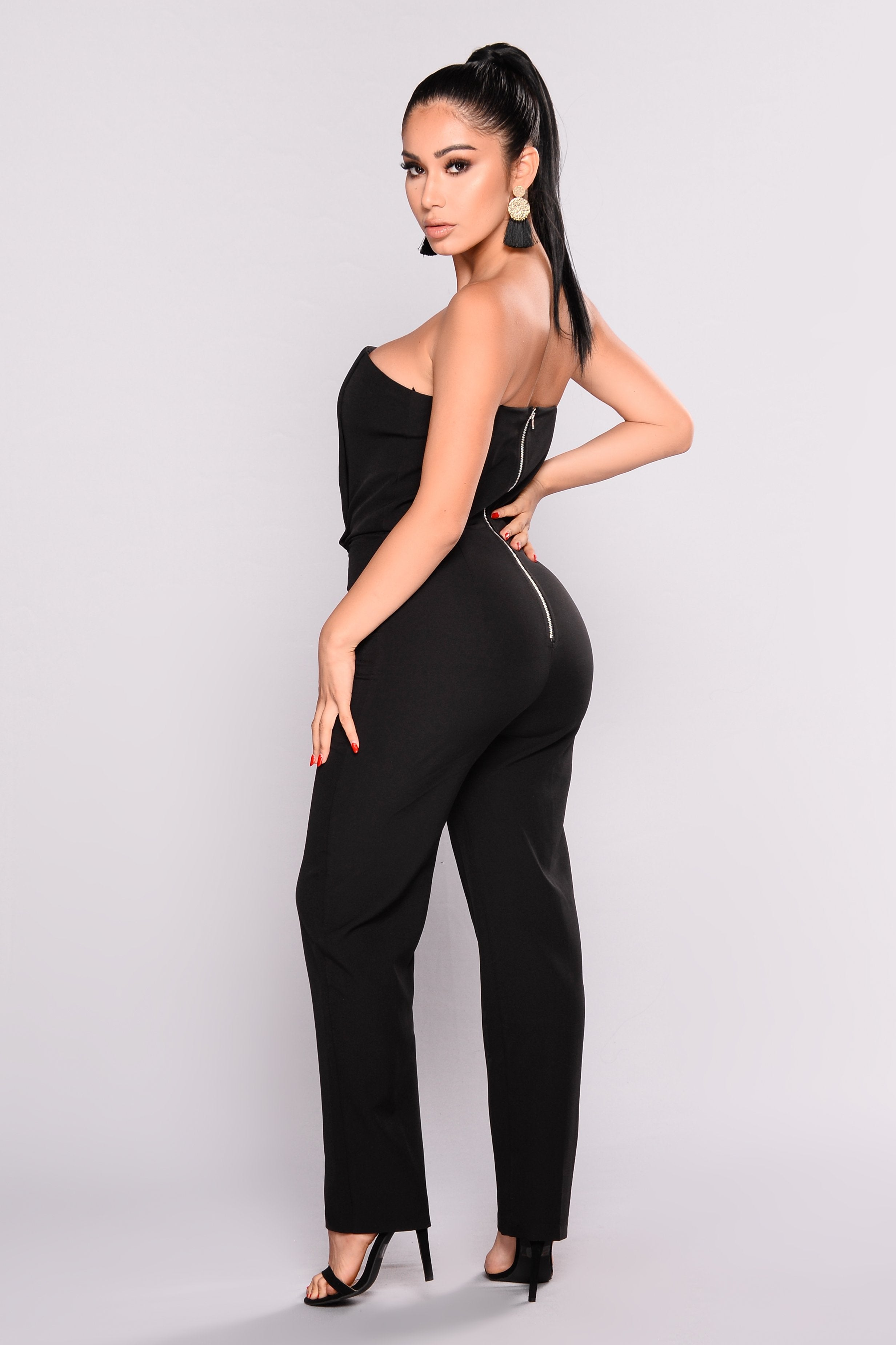 Side profile of model wearing a black, strapless tube jumpsuit by Fashion Nova.