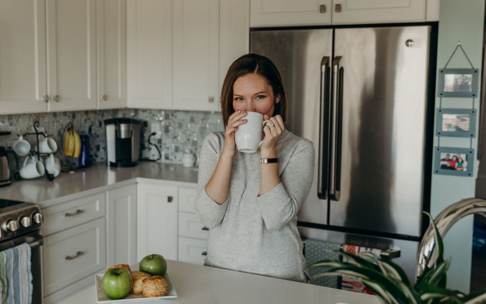 White woman drinking coffee in kitchen