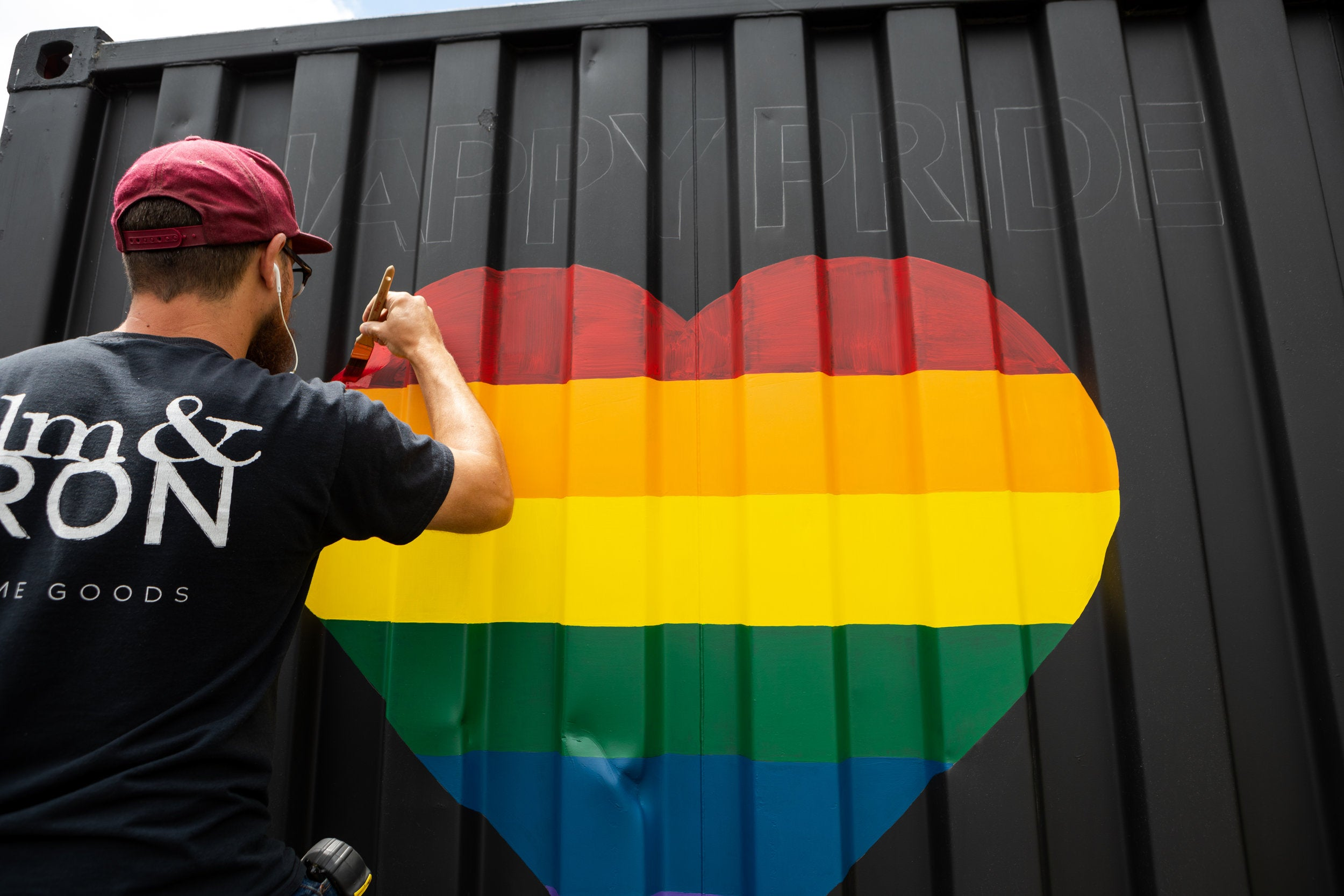 "Tony, painting ""Happy Pride"" on one of our elm & IRON trailers."