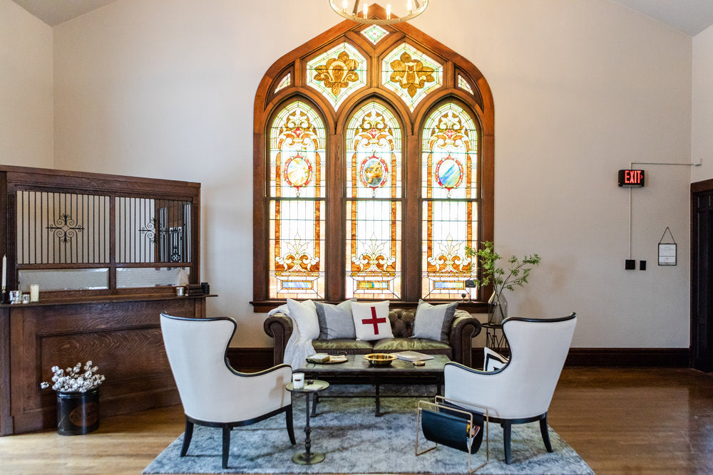 White chairs and couch with stained glass windows