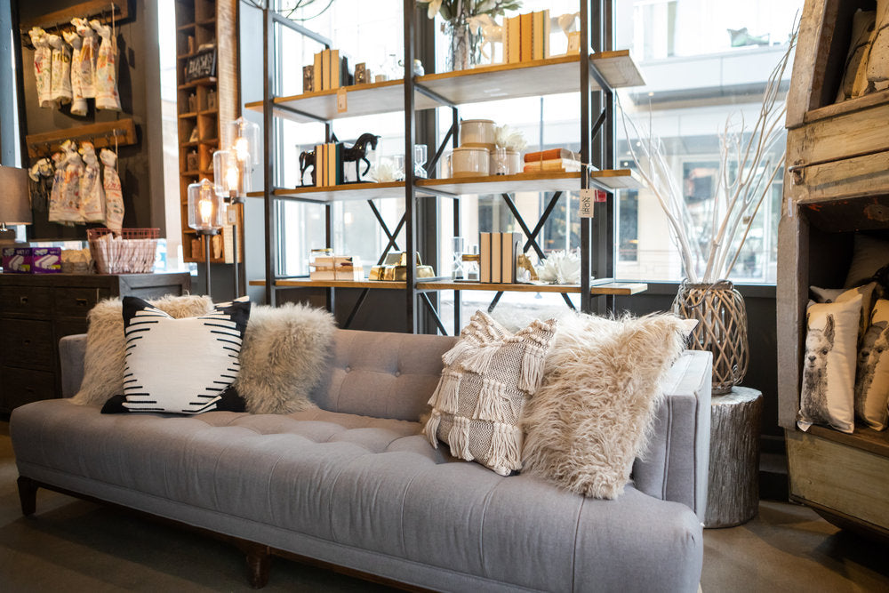 Grey couch with fluffy light throw pillows