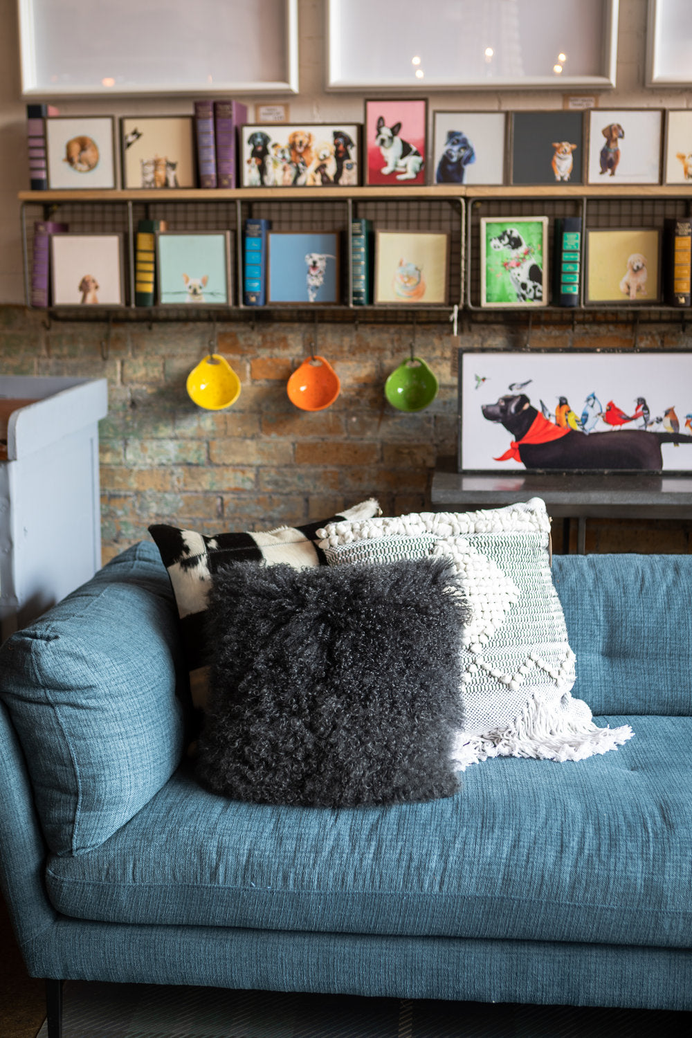 Blue couch with dark and light fluffy pillows