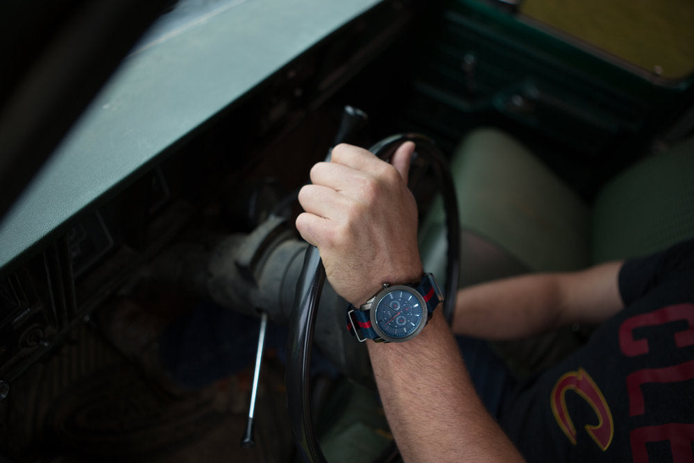 Hand with watch on steering wheel