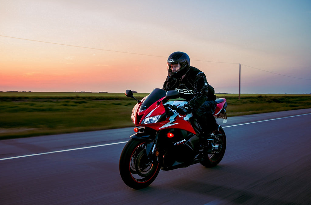 MC Motoparts Riding motorcycle in sunset
