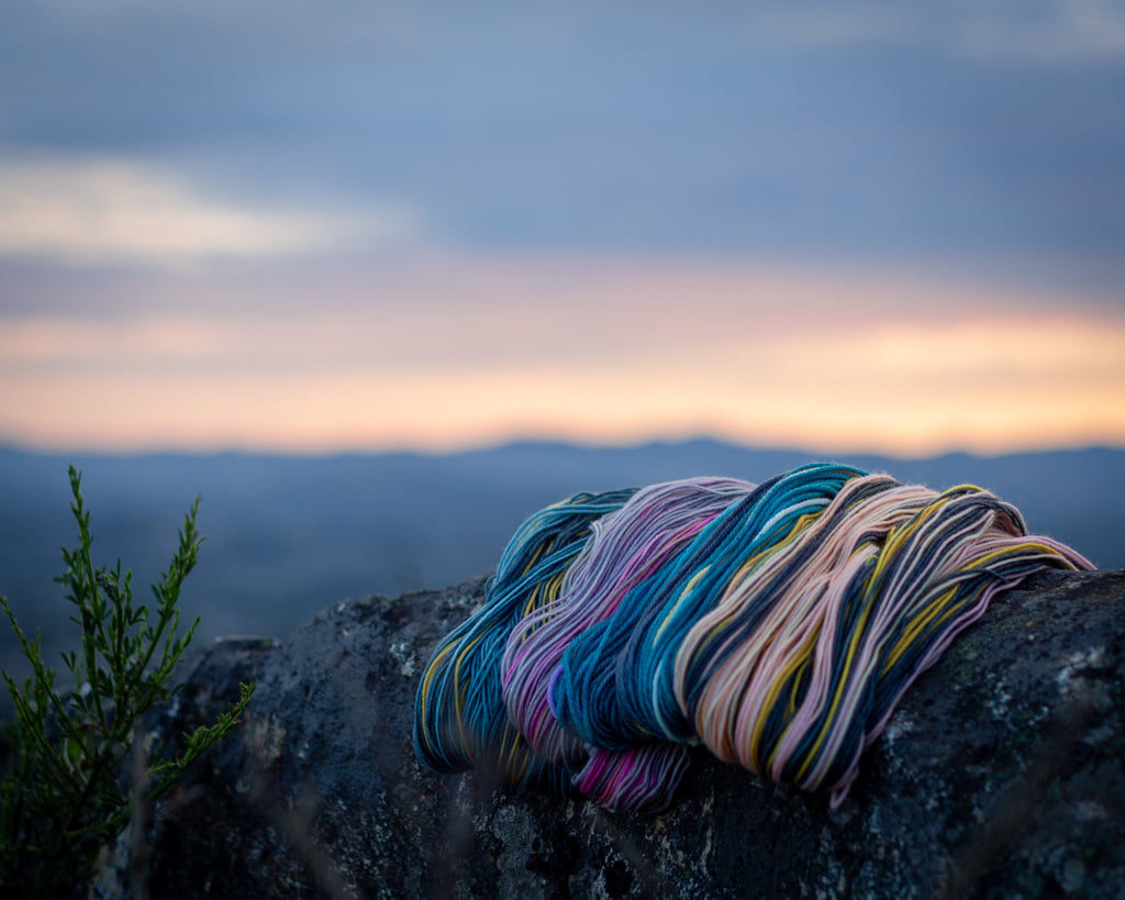 yarn sits on a rock in front of a sunset gauge dye works self striping