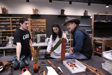 The team at Ethos Custom Brands deciding the final touches on a guitar strap in the shop in Fort Smith, Arkansas.
