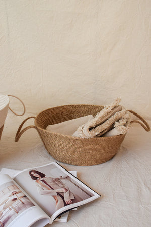 Natural jute basket with a linen blanket inside