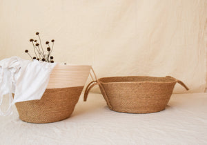 two jute baskets, one of them with flowers inside