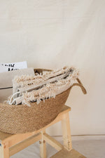Natural jute basket with a blanket and a magazine inside