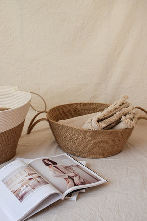 Natural jute basket with blanket inside and a magazine next to it