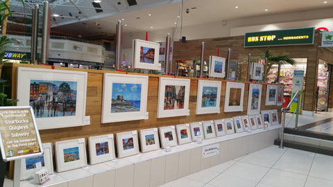 Framed limited edition prints by artist Chris McMorrow for sale on display at the Nutgrove Arts Festival