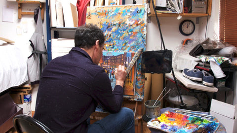 Artist Chris McMorrow working on a painting on an easel in his studio