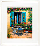 A framed print of a painting of a table and chairs set for an afternoon snack in the South of France