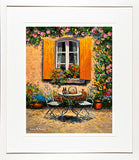 A framed print of a painting of an ornate garden table and chairs outside a yellow shuttered window on a sunny afternoon