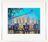 A framed print of a painting of McSorleys Pub on the corner of the main street through Ranelagh village in Dublin