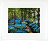 A framed print of a painting of two lovers taking a stroll along a path among the bluebells in a wood