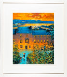 A framed print of a painting of a view from high above the town of Kinsale, Co Cork as the sun is setting