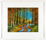 A framed print of a painting of two people walking among the fallen leaves in a wood in autumn