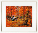 A framed print of a painting of two lovers on a bench in an autumnal forest setting