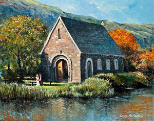 An acrylic painting of the pretty stone church at Gougane Barra, Co Cork, a couple sit on a bench in the foreground.