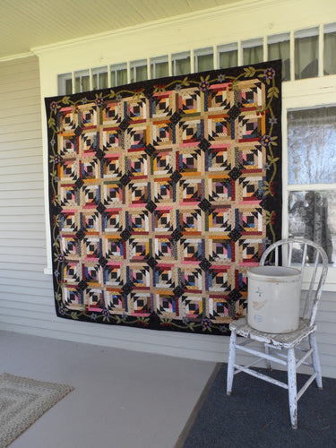scrappy lap quilt pattern with floral applique accent