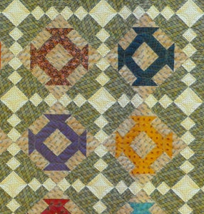 scrappy churn dash blocks make up this scrappy lap quilt