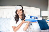 A woman sitting in bed holding a box of Vasanti Do it in Bed Skincare - Night Time Skincare Routine
