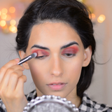 A girl applying eyeshadow using Vasanti Stubby Brush Line Eyeshadow 603